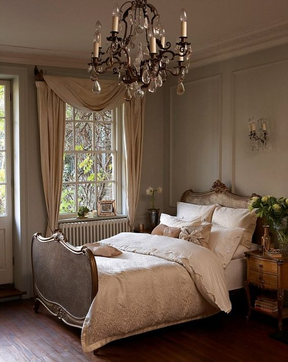 a chic vintage bedroom with a gorgeous bed, a crystal chandelier, neutral textiles and potted plants is lovely