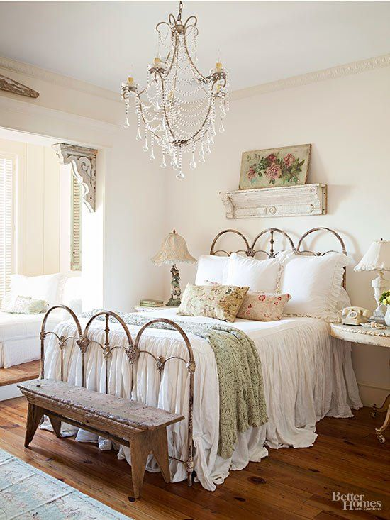 a chic vintage bedroom with a shabby chic bed, a crystal chandelier, some floral bedding and artworks plus shutters looks shabby chic