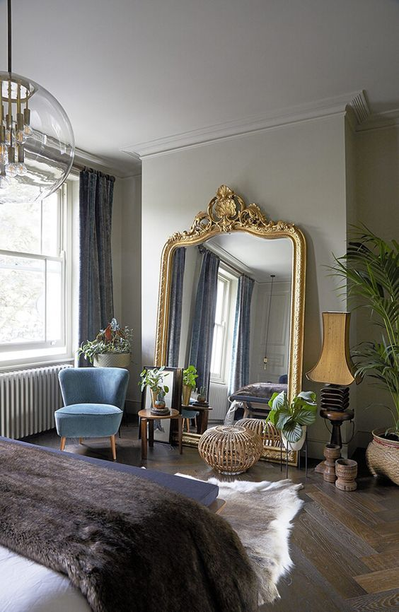 a chic vintage bedroom with an oversized mirror in a chic gold frame, potted greenery, a chandelier and some vintage lamps
