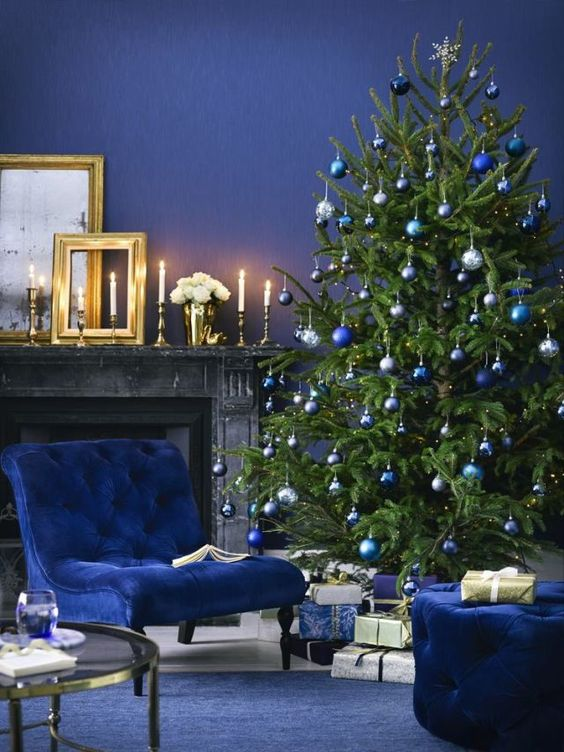 a christmas tree with silver, bold blue and navy ornaments plus navy furniture and walls for a monochromatic holiday space