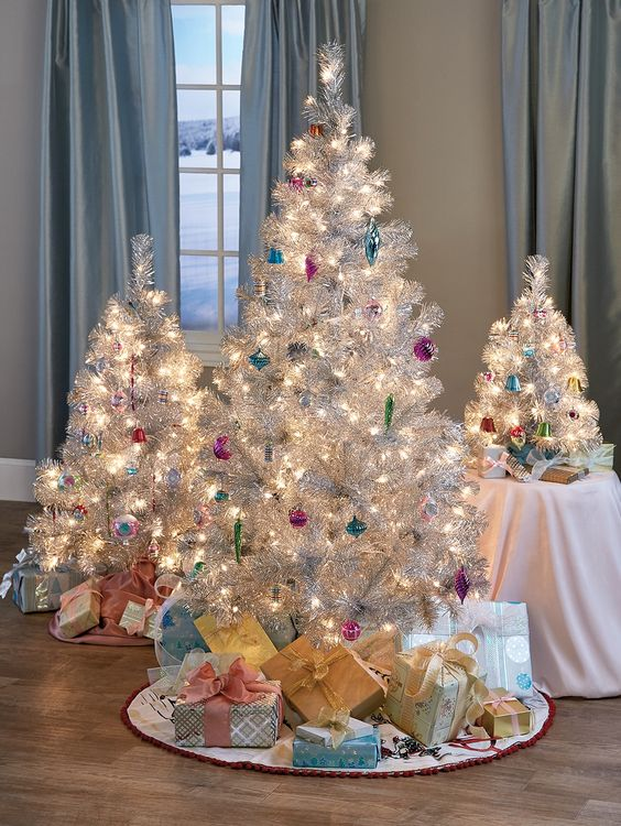 a cluster or silver Christmas trees decorated with colorful ornaments and lights, with stacks of gift boxes for refined holiday decor