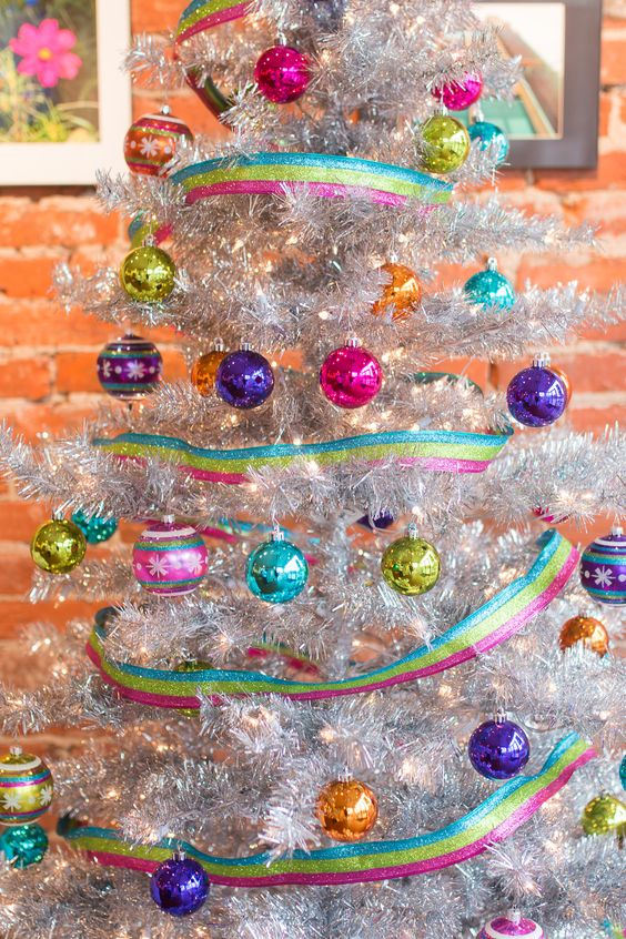 a colorful Christmas tree in silver, with lights, colorful ornaments and rainbow striped ribbons is a lovely and super bold idea
