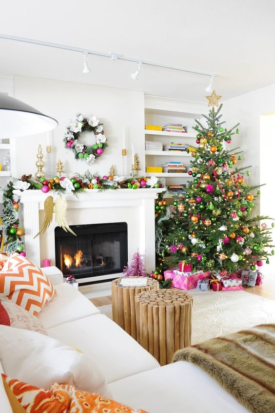 a colorful modern glam Christmas tree with lights and colorful ornaments, a colorful ornament garland on the mantel and bright mini trees