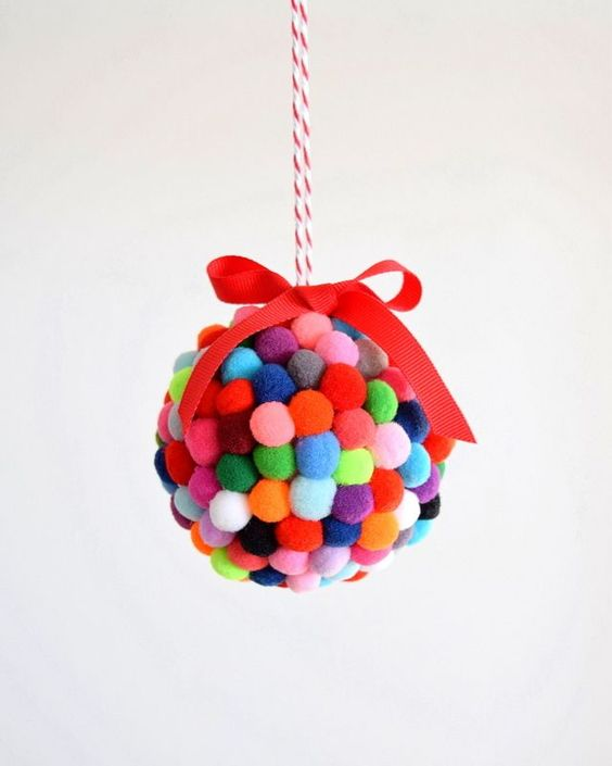 a colorful pompom Christmas ornament with a pretty red bow on top is a lovely decoration to incorporate some color into holiday decor