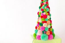 a colorful pompom Christmas tree of a large size with a green bow on top is a fun and old idea