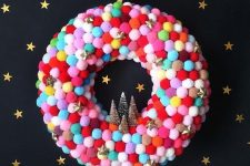 a colorful pompom Christmas wreath with gold glitter stars and tinsel trees is a great idea for front door decor