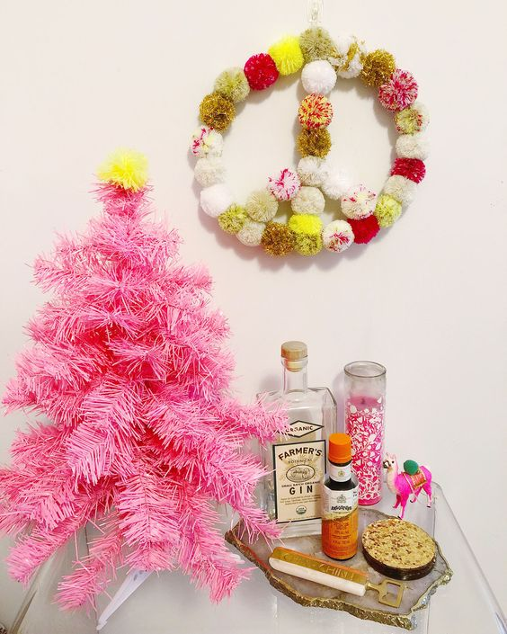 a colorful pompom wreath for boho Christmas decor is a cool and easy craft for winter holidays