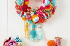 a colorful pompom wreath with bright bells and gold bows plus colorful tassels and a deer is lovely for the holidays