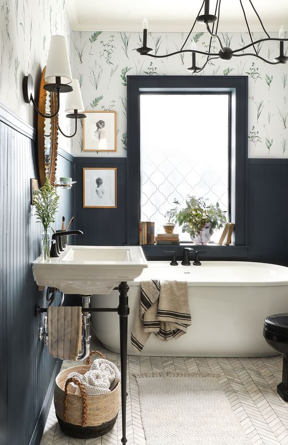 a contrasting bathroom with dark paneling, botanical wallpaper, a sink on dark legs, sconces and a large chandelier