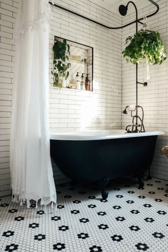 a contrasting black and white bathroom with a floral floor, a black clawfoot tub and potted greenery and black fixtures