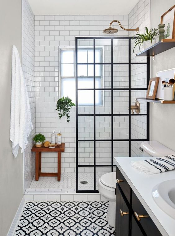 a contrasting black and white bathroom with white subway tiles and printed tiles, a black vanity, a framed screen and brass touches