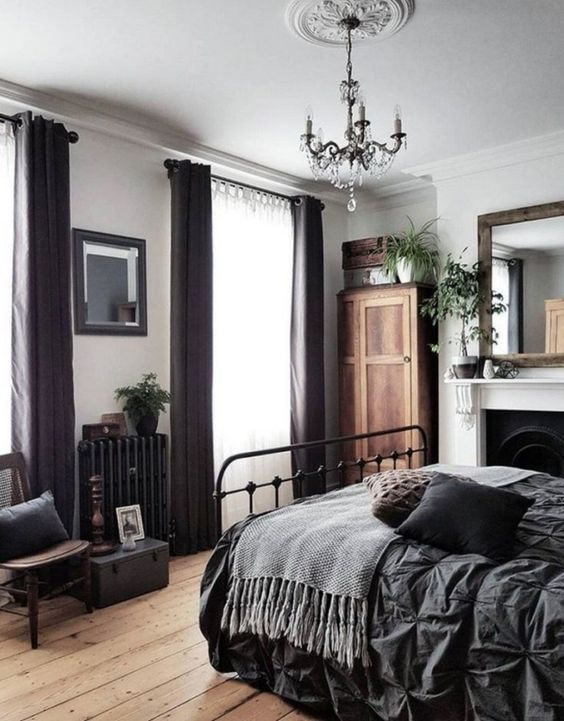 a contrasting vintage bedroom with a metal bed, vintage furniture, dark curtains, potted greenery and a chic crystal chandelier