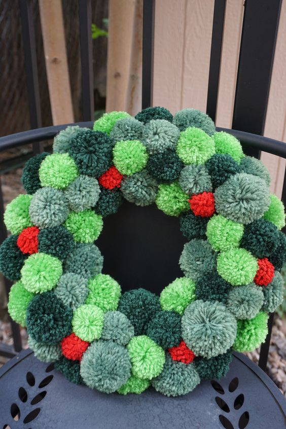 a cool Christmas wreath of pompoms of various shades of green and red is a very Christmassy craft and decoration to rock