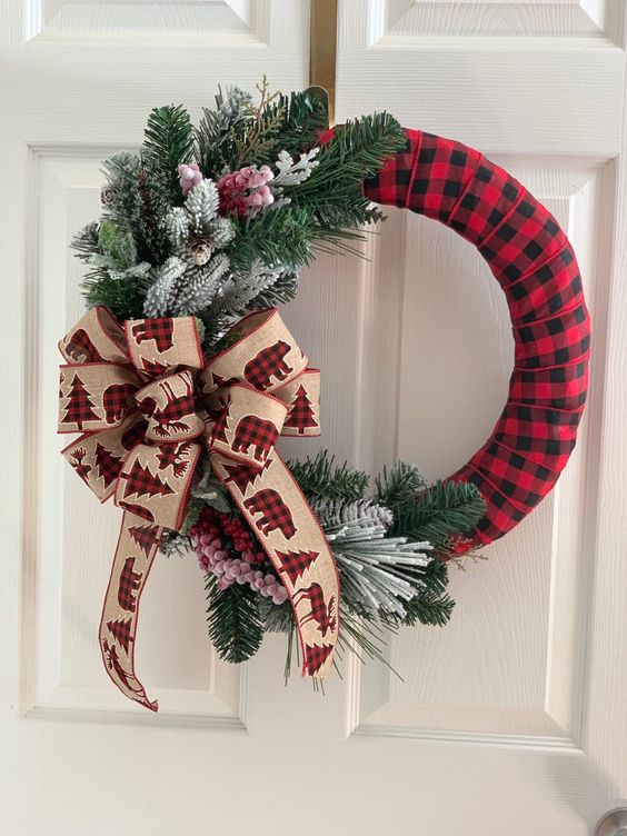a cool Christmas wreath wrapped in plaid, with flocked and usual fir branches and a large bow with plaid bears is amazing