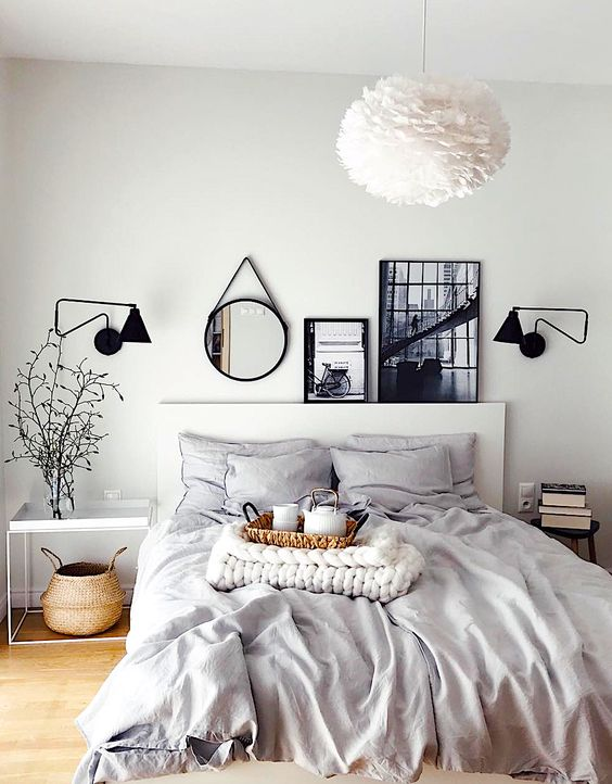 a cool Nordic bedroom with white and black furniture, black sconces, artworks and a mirror over the bed and a fluffy paper lamp