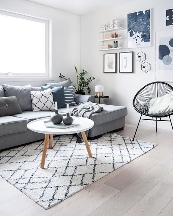 a cool Scandinavian living room with a grey sectional, a black chair, a round table and a bold geometric gallery wall plus a shelf on the wall