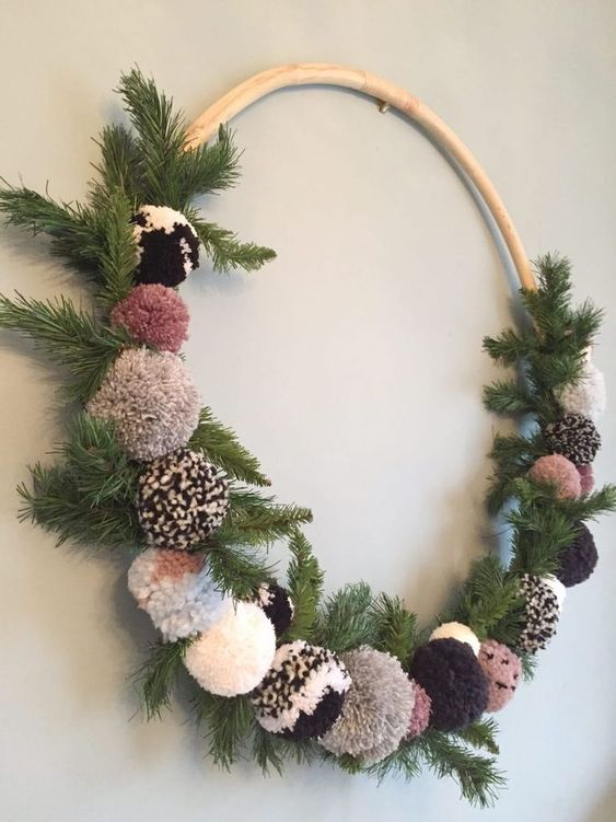 a cozy Christmas wreath of fir branches and pretty ombre and neutral-colored pompoms is a lovely craft for the holidays