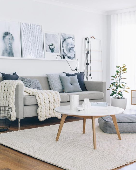 a cozy Nordic living room with a grey sofa, blue pillows and a chunky blanket, a ledge with artworks, some lights and a floor cushion