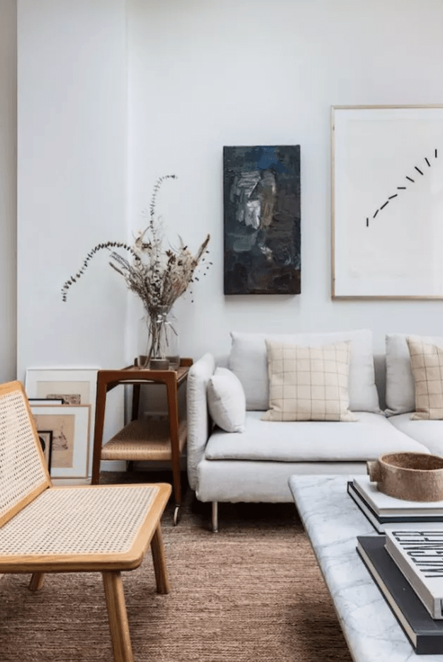 a cozy Scandinavian living room with an off-white sofa, a rattan chair, a woven cart, dried blooms and artworks feels comfy