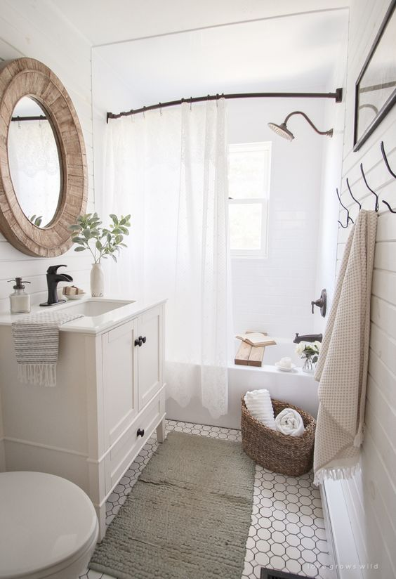 a cozy neutral farmhouse bathroom with beadboard walls, a vintage vanity, a wood frame mirror, a stick with a curtain and neutral linens