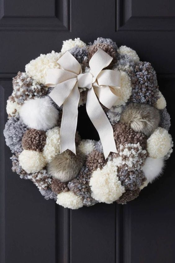 a cozy neutral pompom and faux fur wreath with a large bow is a very warming and cool decoration for your front door