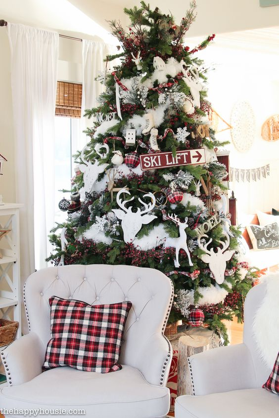 a cozy rustic Christmas tree with white fur, deep ornaments, plaid ones, snowflakes, branches with berries is a great idea