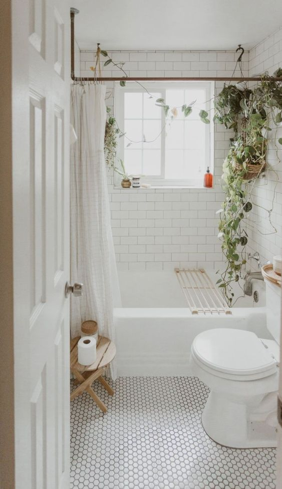 a cozy tiny bathroom clad with marble hex tiles and white subway ones, potted greenery and a wooden stool is a stylish and welcoming space