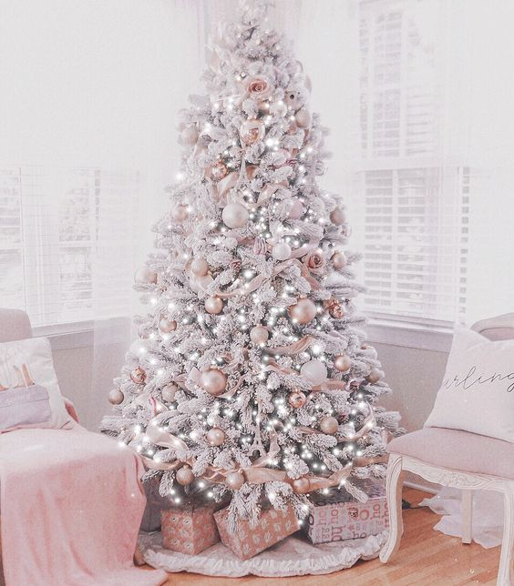 a delicate and refined glam Christmas tree with white and pink ornaments, with lights, flowers and ribbons is just jaw-dropping