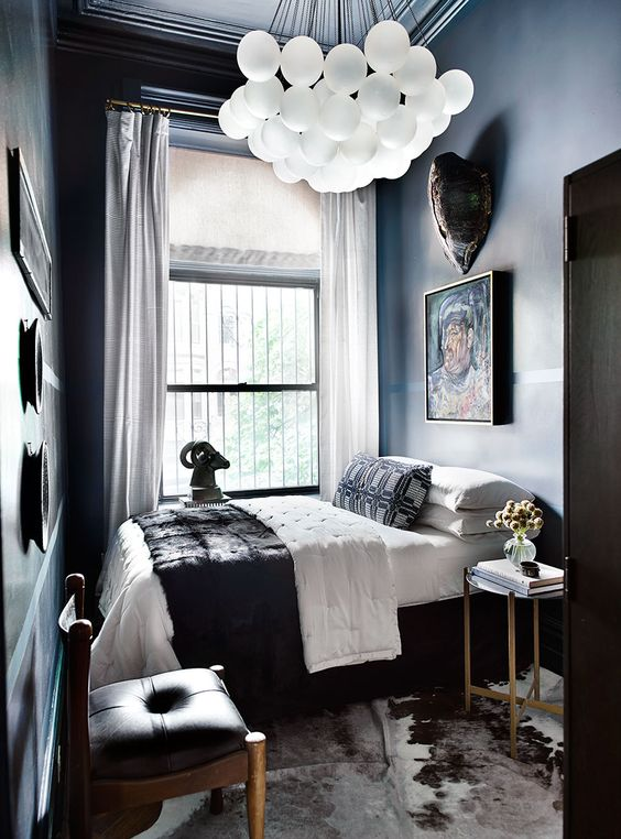 a dramatic and small bedroom with dark walls and a ceiling, dark and chic furniture, a cluster chandelier and a gallery wall