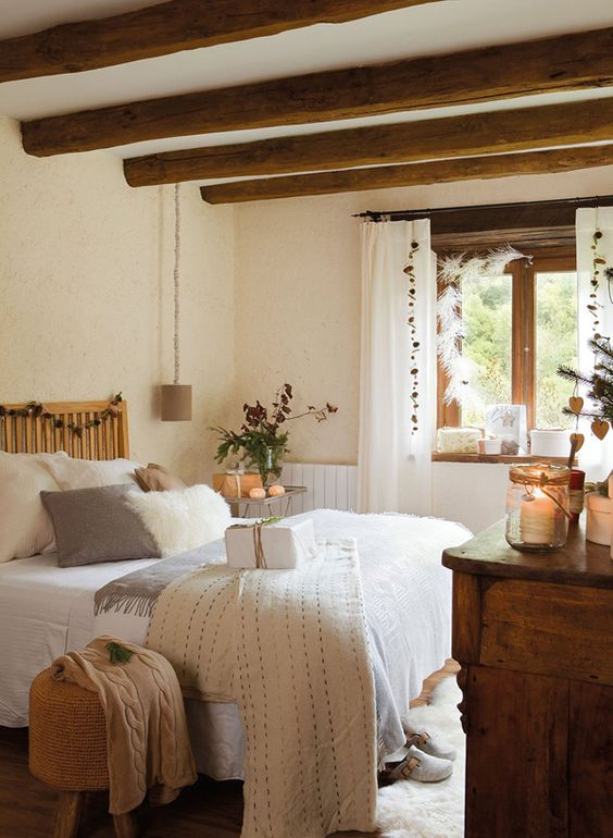 a farmhouse bedroom with wooden beams on the ceiling, wooden furniture, neutral bedding and candle lanterns is very cozy