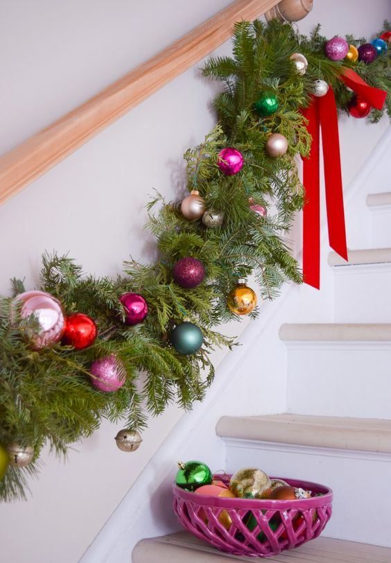 a fir branch garland with colorful Christmas ornaments, bells and red bows is a bold and very cool holiday decor idea
