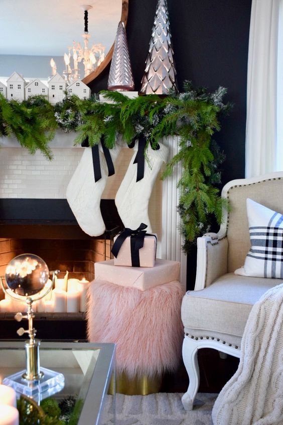 a fir garland, mini houses, silver decorative trees, white stockings with black bows and pink gift boxes for a preppy lam look