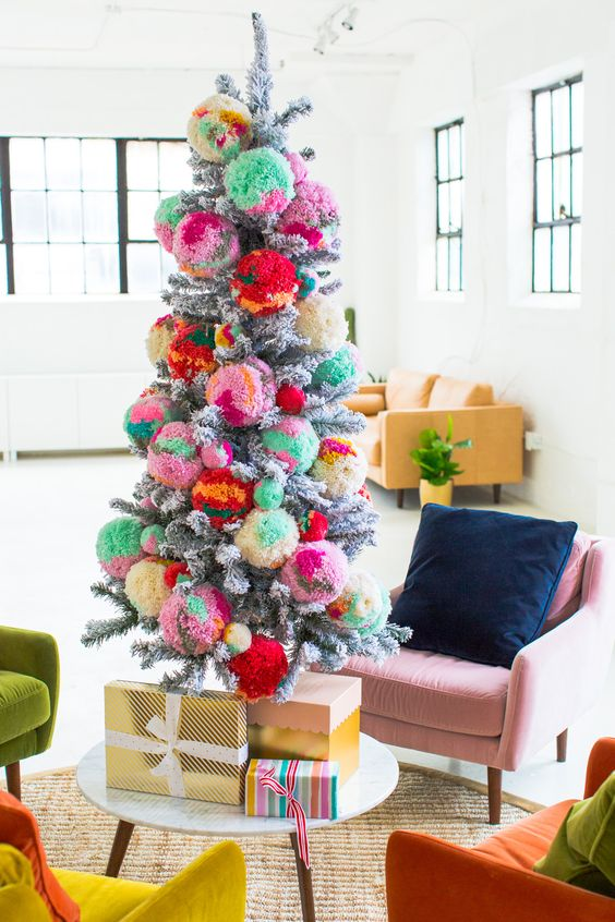a flocked Christmas tree decorated with colorful oversized ombre pompoms insteaf of usual ornaments is a fun idea