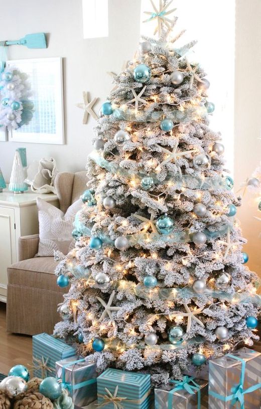 a flocked Christmas tree with lights, silver and tiffany blue ornaments, snowy pinecones and starfish is a fresh idea for a beach Christmas space