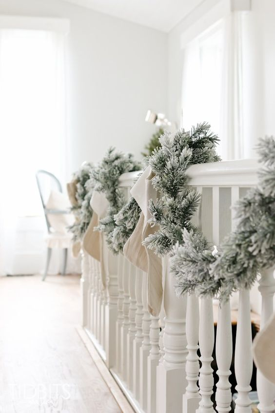 a flocked fir garland with neutral stockings is a pretty and easy vintage rustic staircase decor idea for Christmas