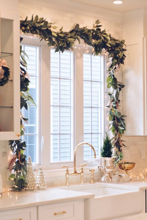 a fresh foliage and light garland framing the window is a lovely idea for a rustic farmhouse space