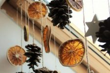 a garland of pinecones and citrus slices is a beautiful and cool idea for decorating your window in natural style