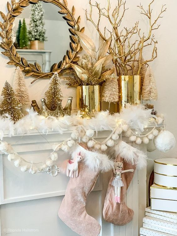 a glam Christmas mantel with whit fur, pink stockings, pompoms, gold tinsel trees, gold vases with leaves and branches