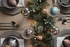 a glam Christmas tablescape with a lush greenery runner, vintage lights, metallic ornaments, grey porcelain and berries is wow