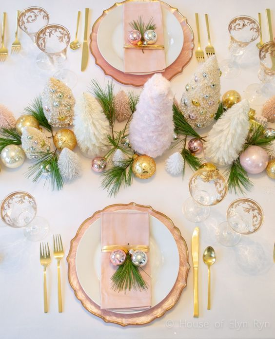 a glam Christmas tablescape with gold, pink and silver ornaments, mini tinsel trees, gold cutlery and fir touches is very chic