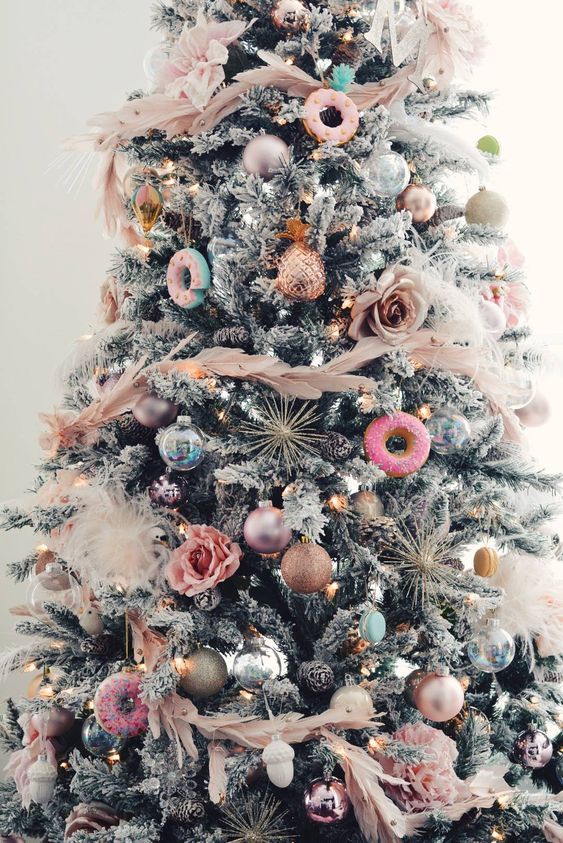 a glam and fun Christmas tree with pink feathers, pink, blue and gold ornaments, blooms and donut ornaments is all fun