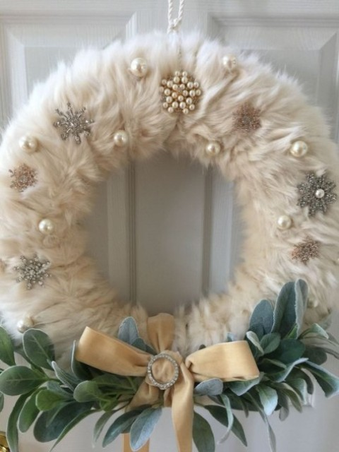 a glam and refined faux fur wreath with large perlas, snowflakes and vintage brooches for holidays can be rocked indoors or outdoors