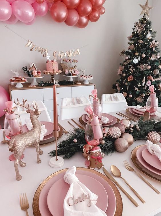 a glam pink Christmas tablescape with pink porcelain, copper cutlery, gold deer and pink ornaments and candles