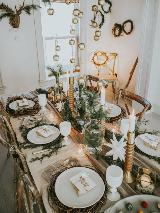 a glam rustic Christmas table setting with greenery, vine placemats, candles, stars, candles in candleholders is wow