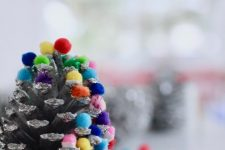 a glitter pinecone with colorful pompoms that add color and fun to it and make it look like a Christmas tree