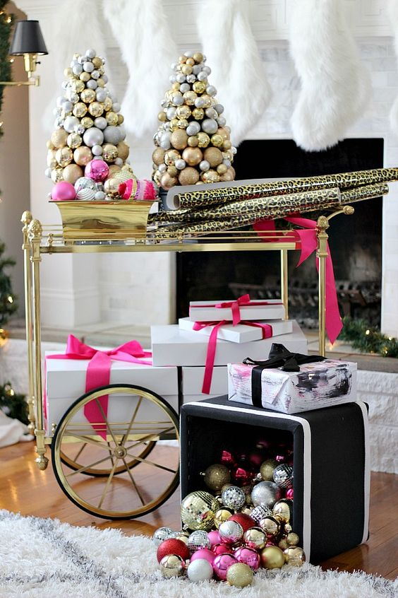 a gold cart with ornament Christmas trees, bright ornaments in a bowl and a box with ornaments lying on the floor