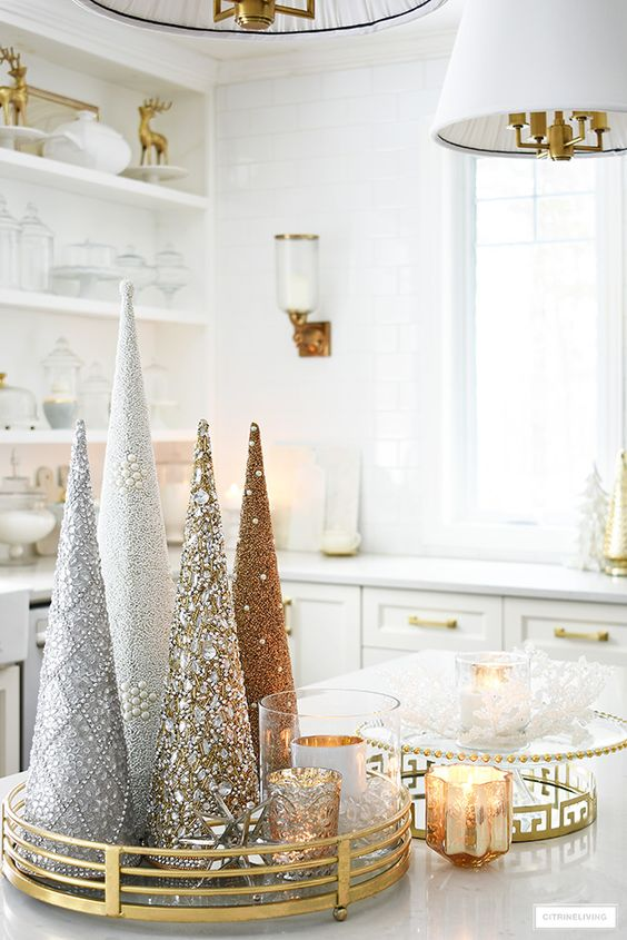 a gold tray with embellished and beaded cone Christmas trees and candles will compose a beautiful winter arrangement