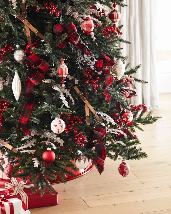 a gorgeous Christmas tree decorated with skis, red and white ornaments, plaid ribbons, berries and with red and white gifts under it