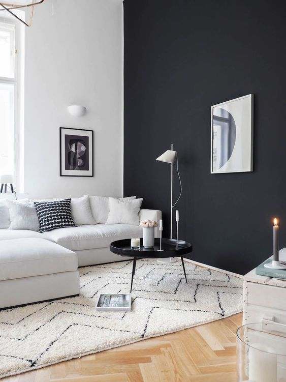 a gorgeous Scandinavian living room with a black wall, a creamy sectional, a black round table, a white wooden chest and lamps