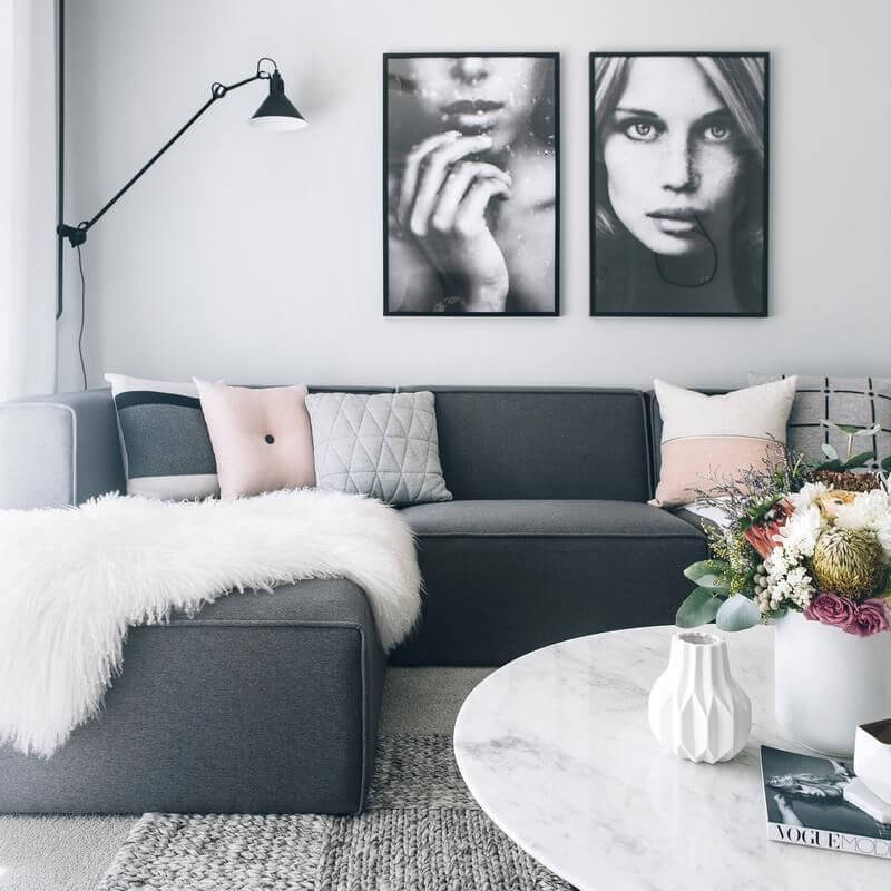 a gorgeous Scandinavian living room with a cool graphite grey sectional, a marble table, black and white artworks and a touch fo color with pillows